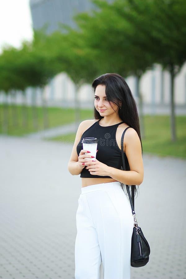 Młoda piękna biznesowa kobieta pije kawowego blisko obok biura obrazy royalty free