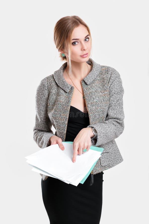 Młoda piękna biznesowa kobieta w czerni sukni, kurtki mienia falcówce, papiery i ono uśmiecha się na szarym tle zdjęcia stock