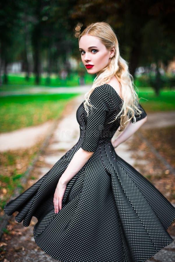 Młoda piękna blond dziewczyna z czerwoną pomadką w jej dużych jaskrawych oczach i robi mu w sukni pozuje na ulicach położenia sło obrazy royalty free
