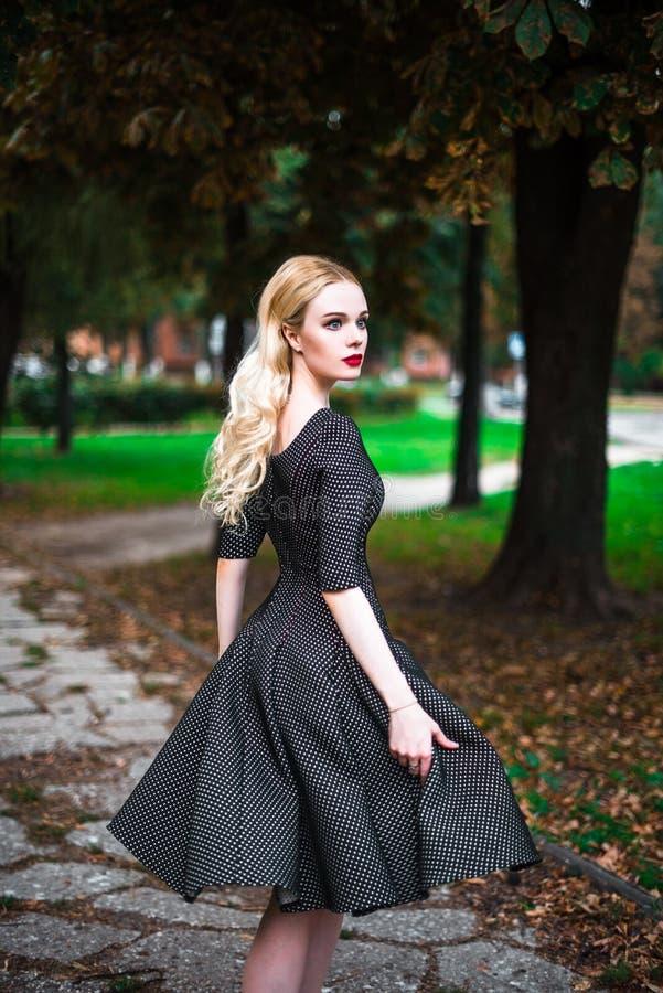 Młoda piękna blond dziewczyna z czerwoną pomadką w jej dużych jaskrawych oczach i robi mu w sukni pozuje na ulicach położenia sło zdjęcie stock