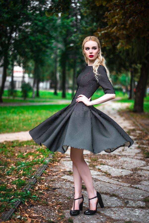 Młoda piękna blond dziewczyna z czerwoną pomadką w jej dużych jaskrawych oczach i robi mu w sukni pozuje na ulicach położenia sło obraz stock
