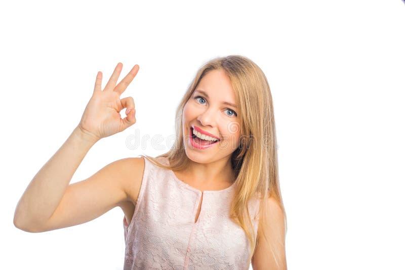 Młoda piękna blond kobieta w sleeveless bluzek przedstawień ok z jeden ręką i uśmiechami strzela w górę odosobnionego dalej, zdjęcia royalty free