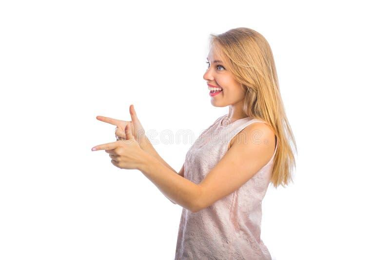 Młoda piękna blond kobiety pozycja w profilu z dwa palcami wskazującymi wskazuje strona, filmuje w górę na obrazy royalty free