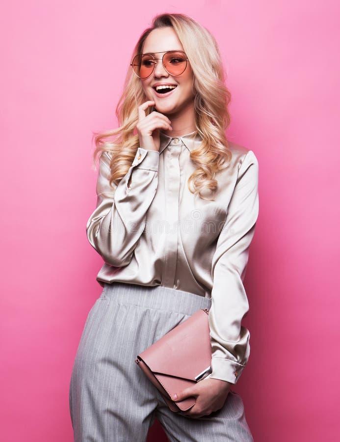 MÅ'oda, piÄ™kna blondynka w bluzce, spodniach i okularach, trzyma torebkÄ™ i pozuje różowe tÅ'o zdjęcie stock