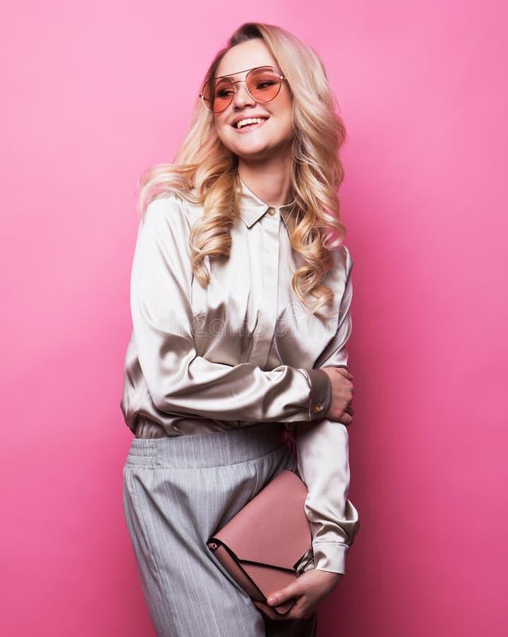 MÅ'oda, piÄ™kna blondynka w bluzce, spodniach i okularach, trzyma torebkÄ™ i pozuje różowe tÅ'o zdjęcia stock