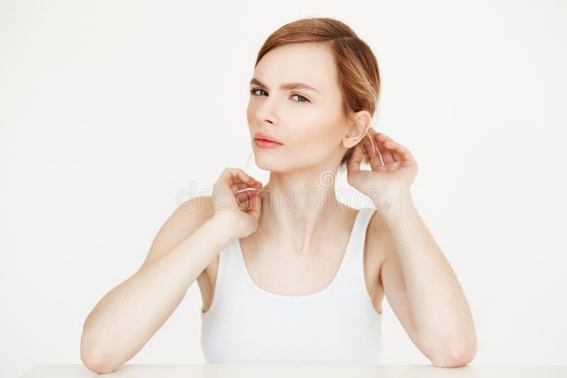 Młoda piękna blondynki dziewczyna patrzeje kamery obsiadanie przy stołem nad biały tła korygować z czystą świeżą skórą obraz stock