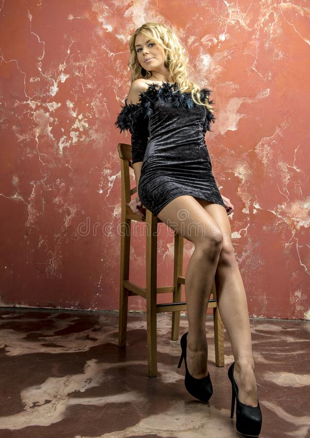 Młoda piękna blondynki dziewczyna w czarnej koktajl sukni zdjęcie royalty free