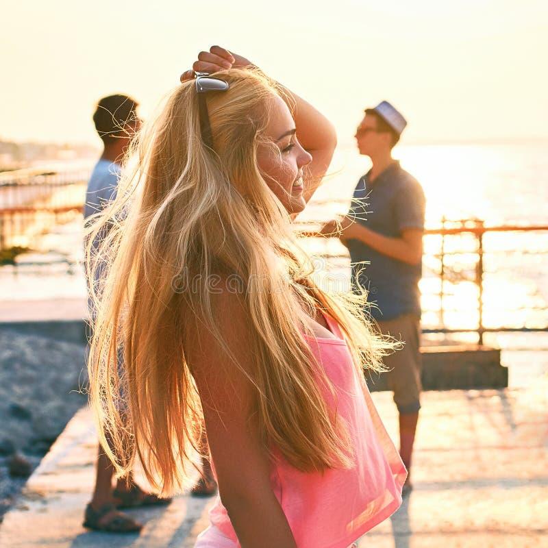 Młoda piękna blondynki dziewczyna w menchiach nakrywa mieć zabawę przy wieczór nadmorski z jej przyjaciółmi na tle zdjęcie stock