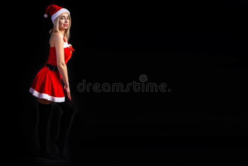 Młoda piękna blondynki dziewczyna w seksownym czerwonym Śnieżnym Dziewiczym Święty Mikołaj na czarnym odosobnionym tle w bożych n obraz stock