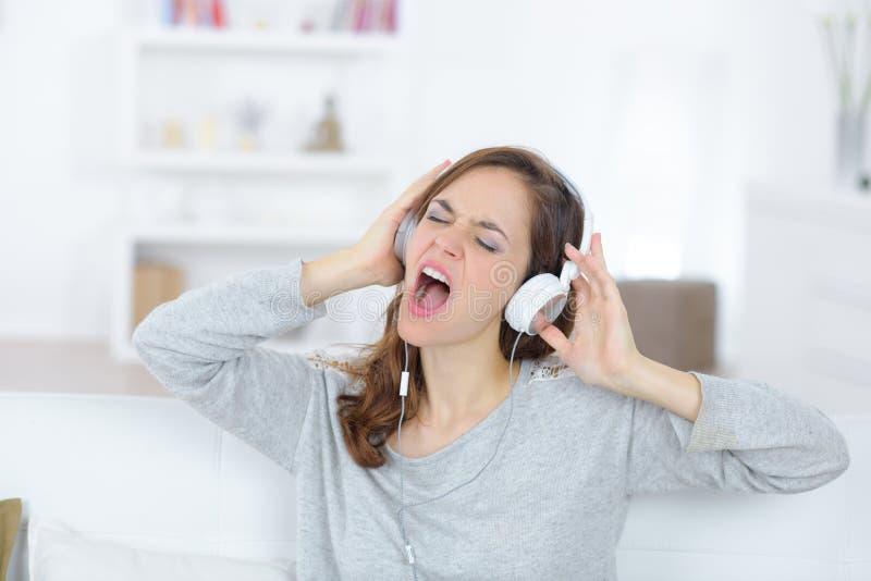 Młoda piękna brunetki dziewczyna ma zabawę słucha metal muzyka fotografia royalty free