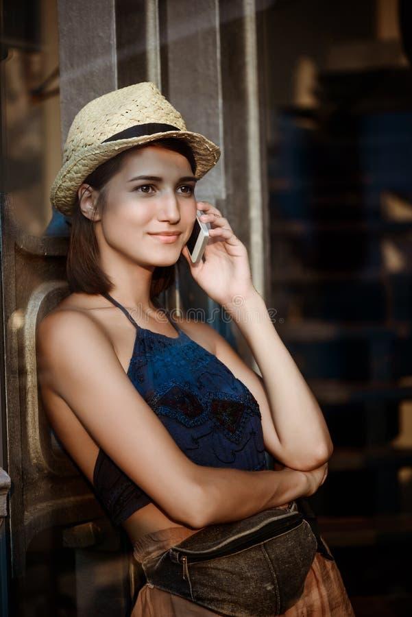 Młoda piękna brunetki dziewczyna w kapeluszowy ono uśmiecha się, mówi na telefonie obrazy royalty free