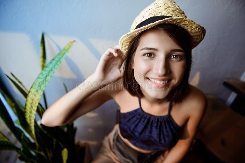 Młoda piękna brunetki dziewczyna w kapeluszowym obsiadaniu na schodkach, ono uśmiecha się zdjęcie stock
