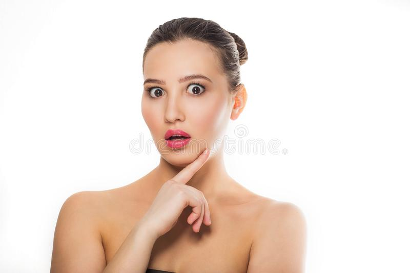 Młoda piękna brunetki dziewczyna z naturalnym makeup, czysta skóra wystawiający nadzy ramiona patrzeje kamerę z usta otwartą ręką obraz stock