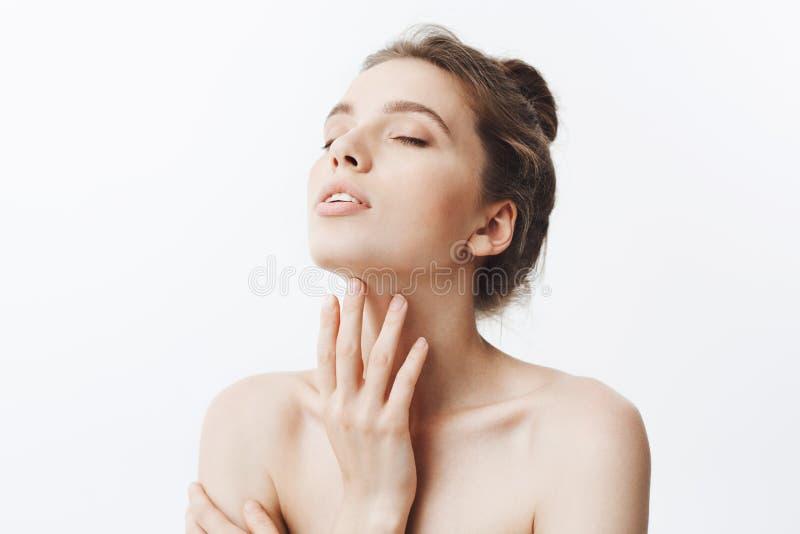 Młoda piękna ciemnowłosa caucasian kobieta napada głowę z zamkniętymi oczami z babeczki fryzurą i nagimi ramionami obrazy stock
