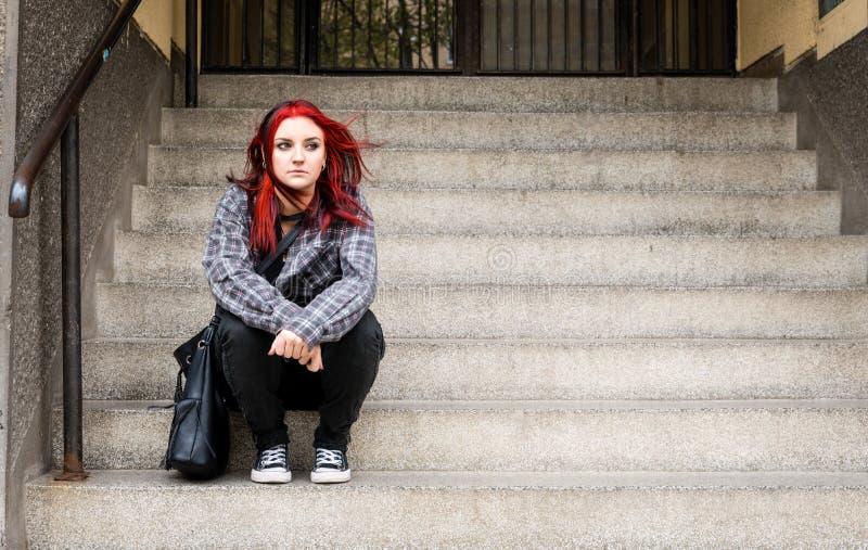 Młoda piękna czerwona włosiana dziewczyna siedzi samotnego outdoors na schodkach budynek z czuciowy niespokojnym i depresse kapel obrazy stock