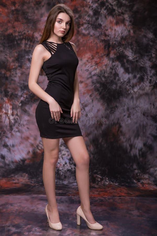 Młoda piękna dama pozuje w krótkiej czarnej ciasnej sukni zdjęcie royalty free