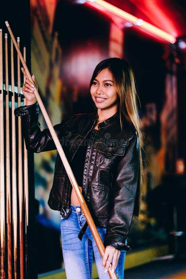 Młoda piękna dziewczyna jest ubranym skórzaną kurtkę w bilardowym klubie z wskazówka kija narządzaniem dla gry, zdjęcie stock