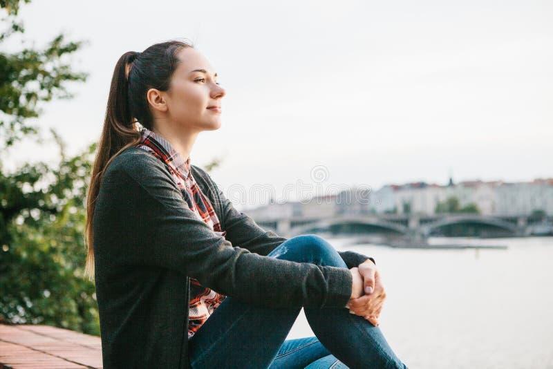 Młoda piękna dziewczyna na banku Vltava rzeka w Praga w republika czech, podziwia pięknego widok i zdjęcie stock