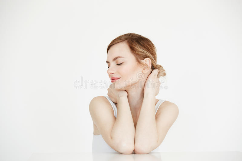 Młoda piękna dziewczyna ono uśmiecha się z zamkniętymi oczami siedzi przy stołem nad białym tłem z perfect czystą skórą Piękno zd fotografia royalty free