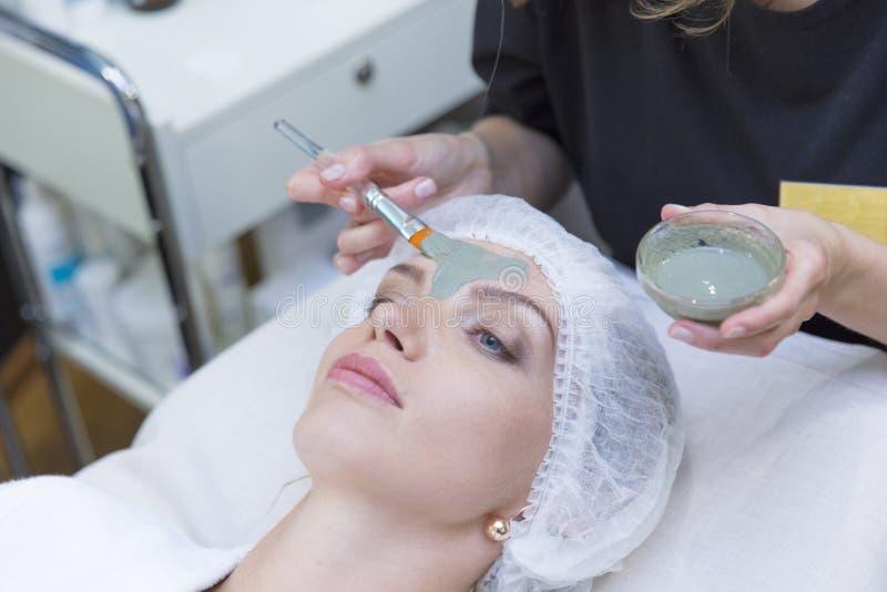 Młoda piękna dziewczyna otrzymywa twarzową maskę od lekarki w zdroju piękna salonie - indoors zdjęcie stock