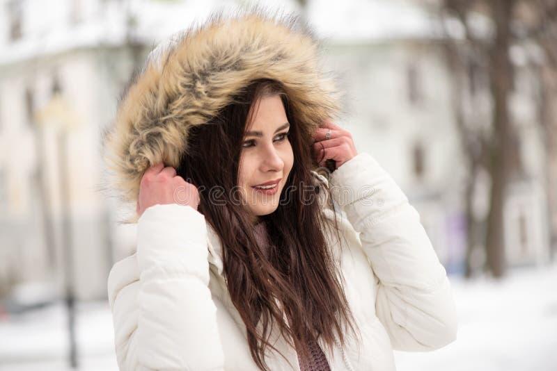 Młoda piękna dziewczyna po środku śnieżnego parka Ciepła i wygodna zima odziewa, zima czas zdjęcia stock