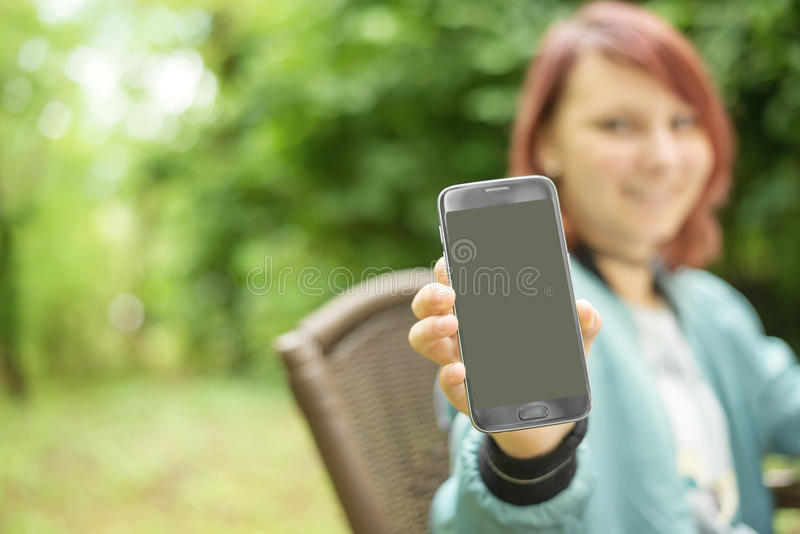 Młoda piękna dziewczyna pokazuje telefon komórkowego z miejscem dla reklamować obraz royalty free