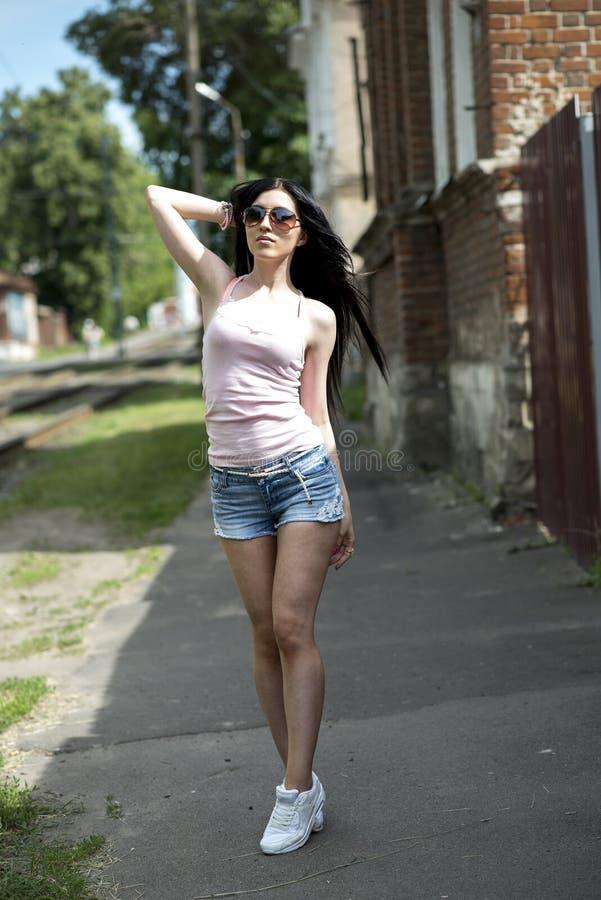 Młoda piękna dziewczyna pozuje mody miasto w krótkich drelichowych skrótach, bluzce i okulary przeciwsłoneczni seksownej kobiecie zdjęcia stock