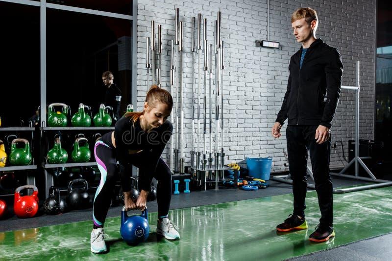 Młoda piękna dziewczyna robi ćwiczeniu z ciężarami pod kierownictwem trenera obraz royalty free