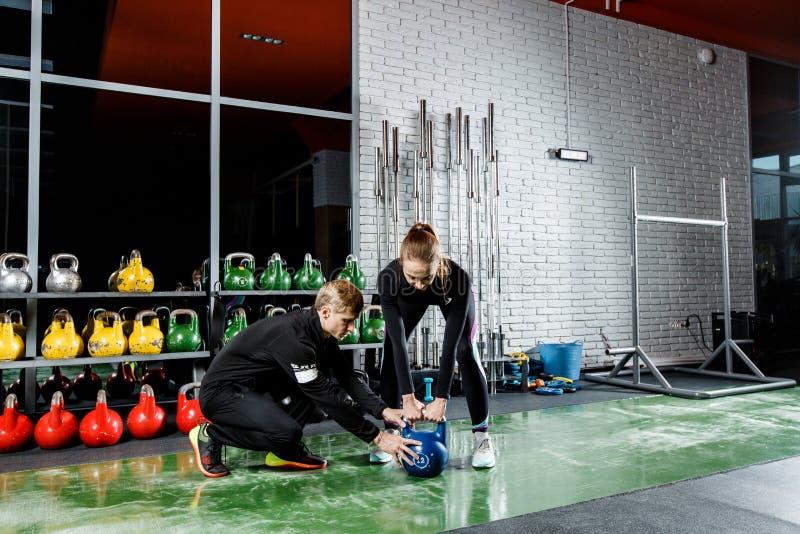 Młoda piękna dziewczyna robi ćwiczeniu z ciężarami pod kierownictwem trenera obrazy royalty free