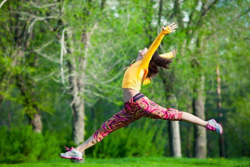 Młoda piękna dziewczyna robi gimnastycznym skokom obraz royalty free