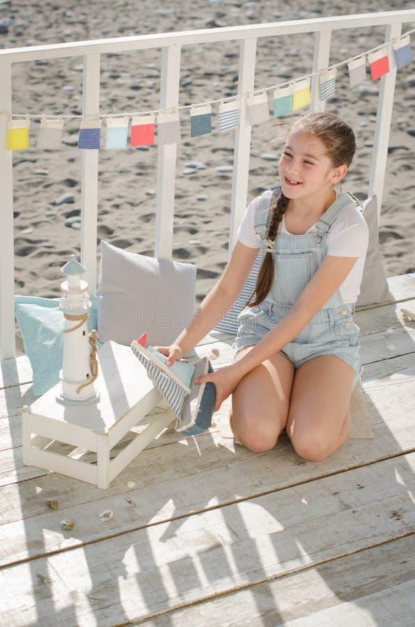 Młoda piękna dziewczyna siedzi na plażowym utrzymanie uśmiechu i zabawkach zdjęcia stock