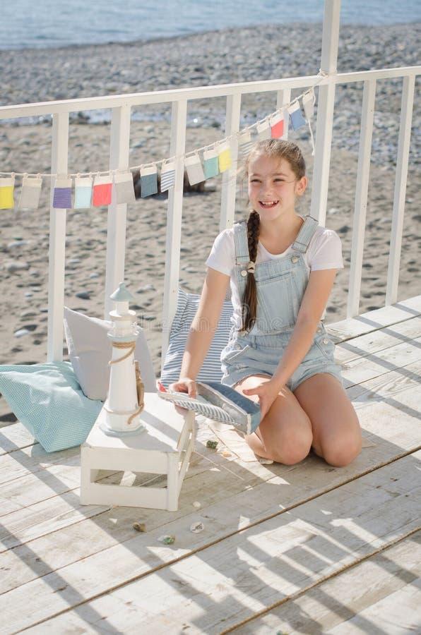 Młoda piękna dziewczyna siedzi na plażowym utrzymanie uśmiechu i zabawkach zdjęcia royalty free