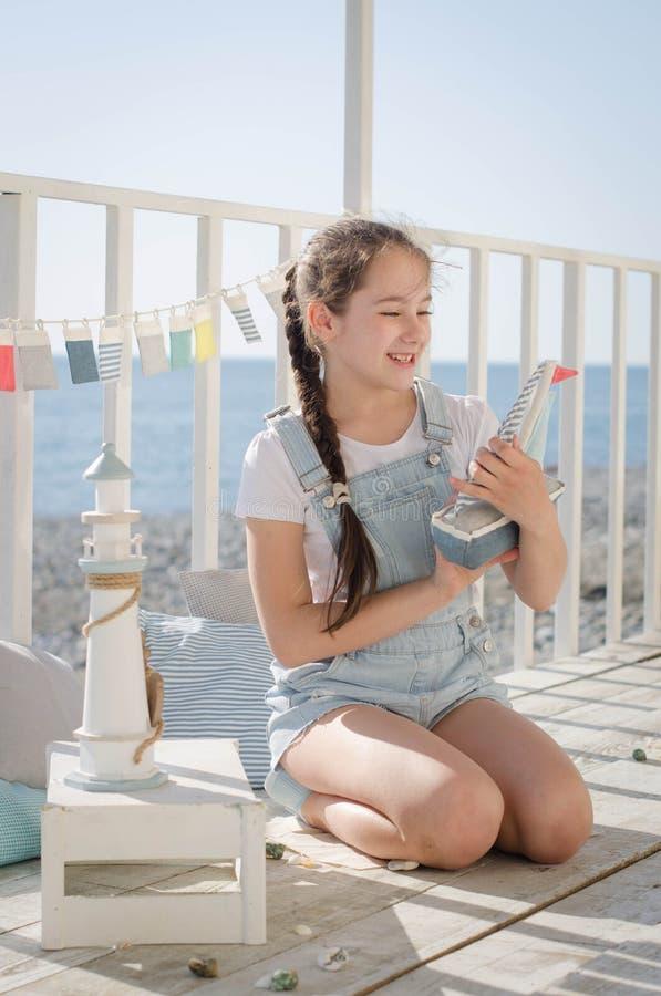 Młoda piękna dziewczyna siedzi na plażowym utrzymanie uśmiechu i zabawkach obraz stock