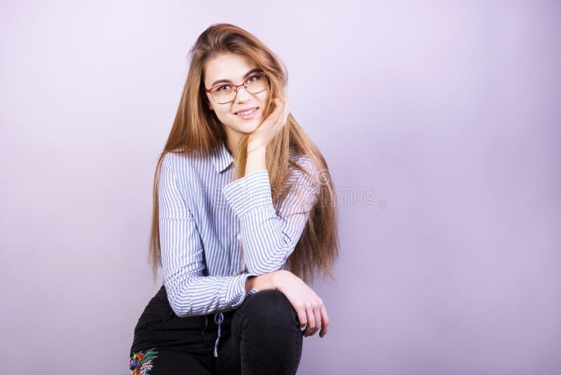Młoda piękna dziewczyna stoi przed popielatym tłem, uśmiecha się koszula i jest ubranym z szkłami, mnóstwo czysty zdjęcia royalty free