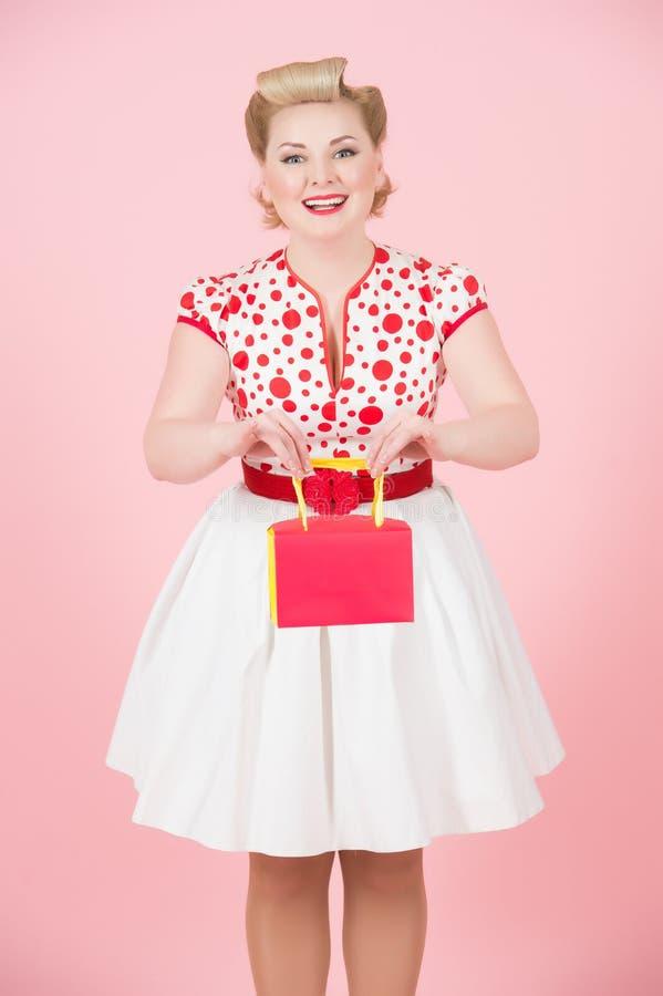 Młoda piękna dziewczyna trzyma czerwieni pudełko odizolowywa w studiu na różowym tle fotografia stock