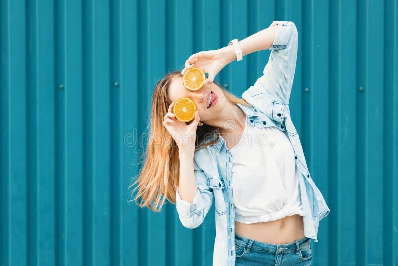 Młoda piękna dziewczyna używa dwa halfs na pomarańczach zamiast szkieł nad jej oczami trzyma jęzor za zdjęcie royalty free