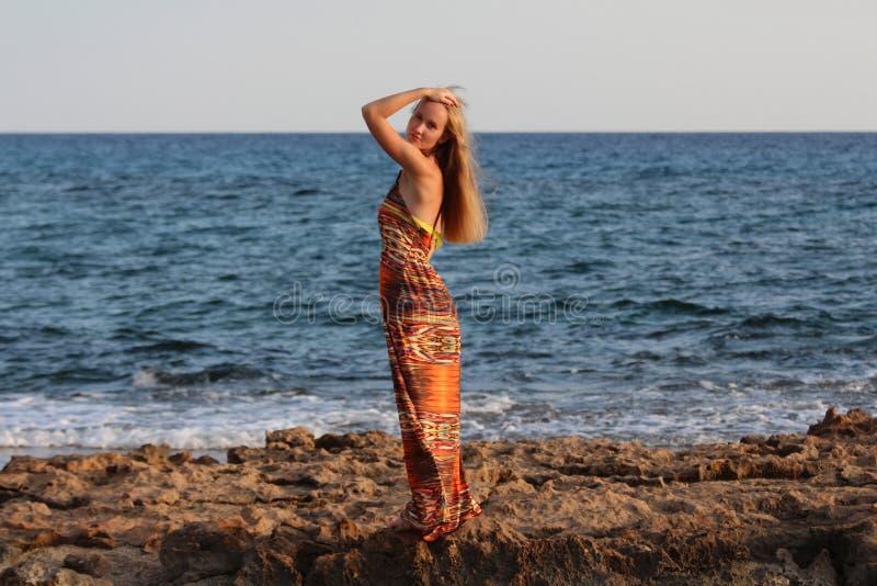 Młoda piękna dziewczyna w długiej sukni i rzucać rękę głowa zdjęcie royalty free