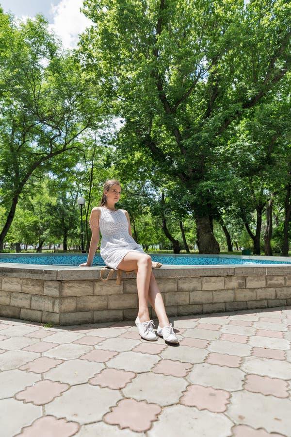 Młoda piękna dziewczyna w krótkiej biel sukni siedzi blisko fontanny fotografia stock