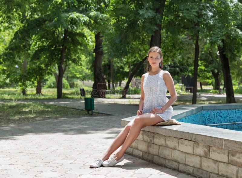 Młoda piękna dziewczyna w krótkiej biel sukni siedzi blisko fontanny obraz royalty free