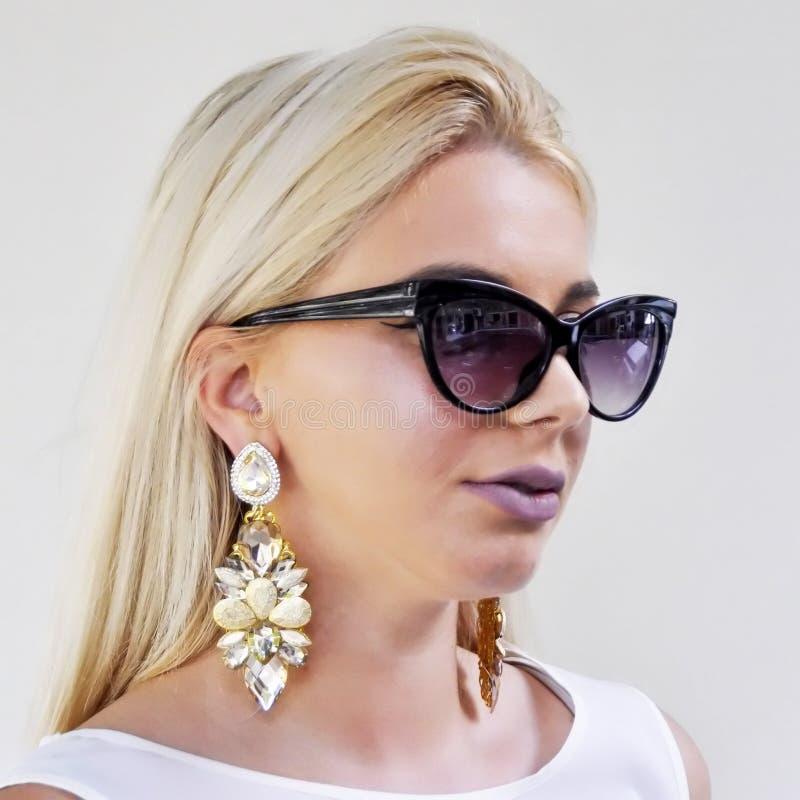 Młoda piękna dziewczyna w słońc szkłach z dużymi kolczykami obrazy royalty free