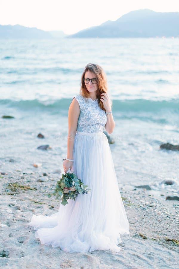 Młoda piękna dziewczyna w szkłach w błękit sukni odprowadzeniu blisko jeziora i Lago Di Garda w Sirmione Włochy zdjęcie stock