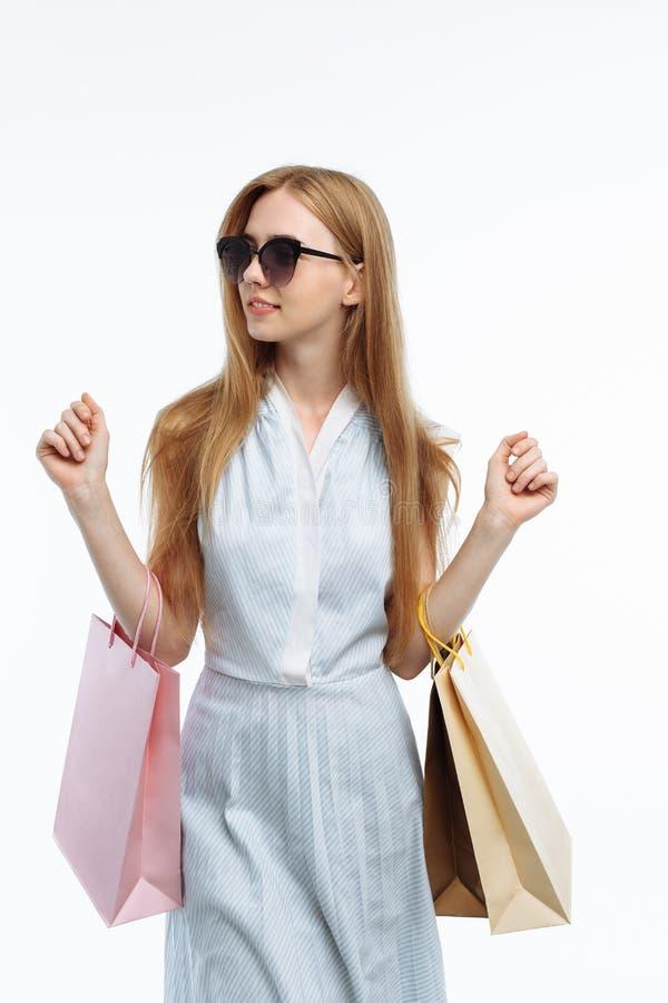Młoda piękna dziewczyna w szkieł robić zakupy zdojest, pozuje z prezentem zdjęcia stock