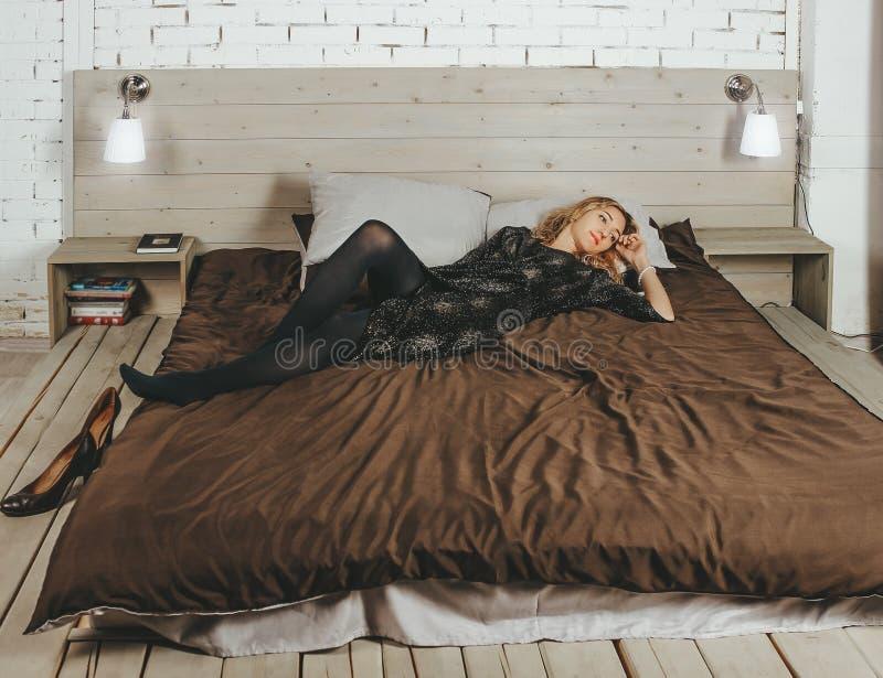 Młoda piękna dziewczyna w wieczór sukni w górę lying on the beach na łóżku po przyjęcia na tle biała ściana z cegieł fotografia royalty free
