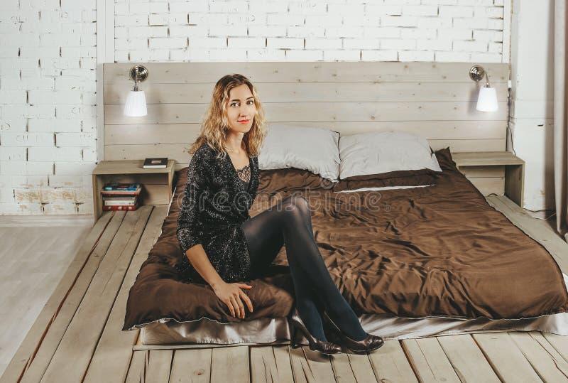 Młoda piękna dziewczyna w wieczór sukni w górę lying on the beach na łóżku po przyjęcia na tle biała ściana z cegieł zdjęcie stock