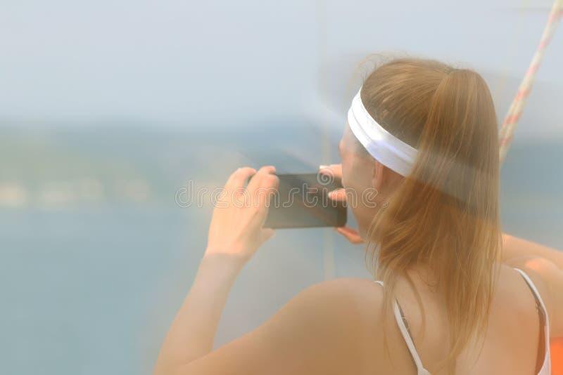 Młoda piękna dziewczyna z brązowowłosą kobietą bierze fotografię smartphone na morzu od strony żeglowanie jacht Fasc zdjęcia royalty free