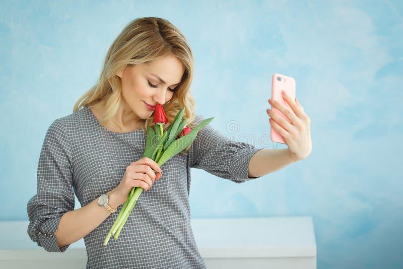 Młoda piękna dziewczyna z bukietem tulipany robi selfie na telefonie zdjęcie stock
