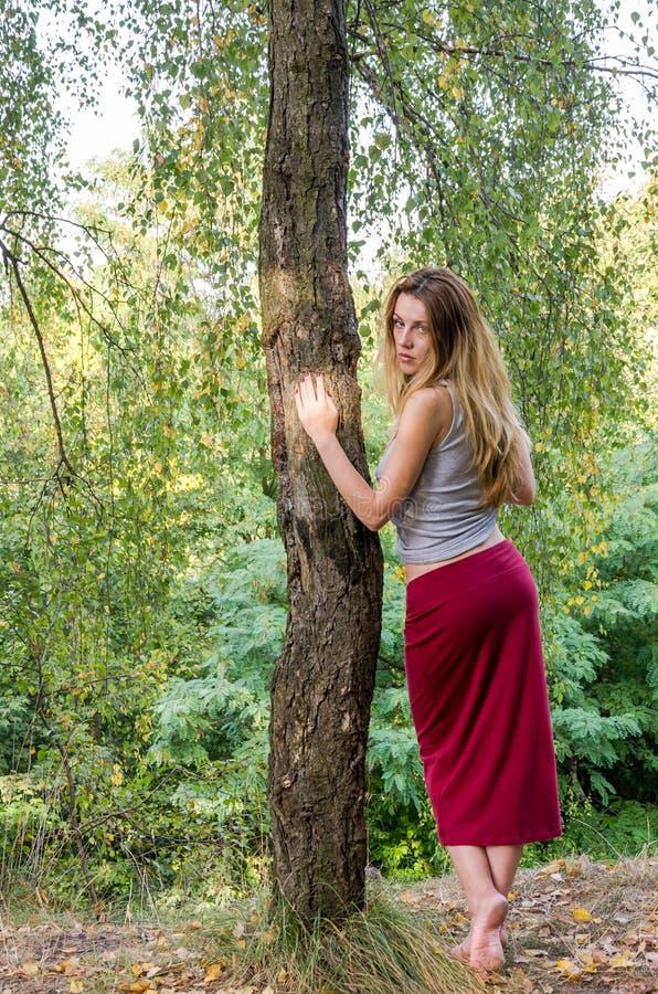 Młoda piękna dziewczyna z długie włosy Europejskimi pojawienie pozami podczas spaceru w parku wśród roślinności i drzew zdjęcie royalty free