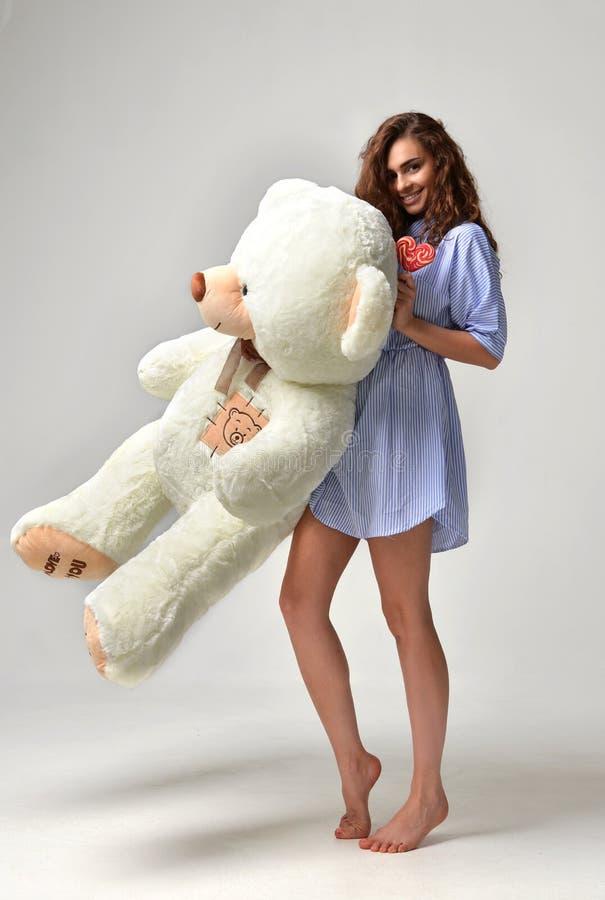 Młoda piękna dziewczyna z dużej miś miękkiej części zabawki szczęśliwy ono uśmiecha się zdjęcie stock