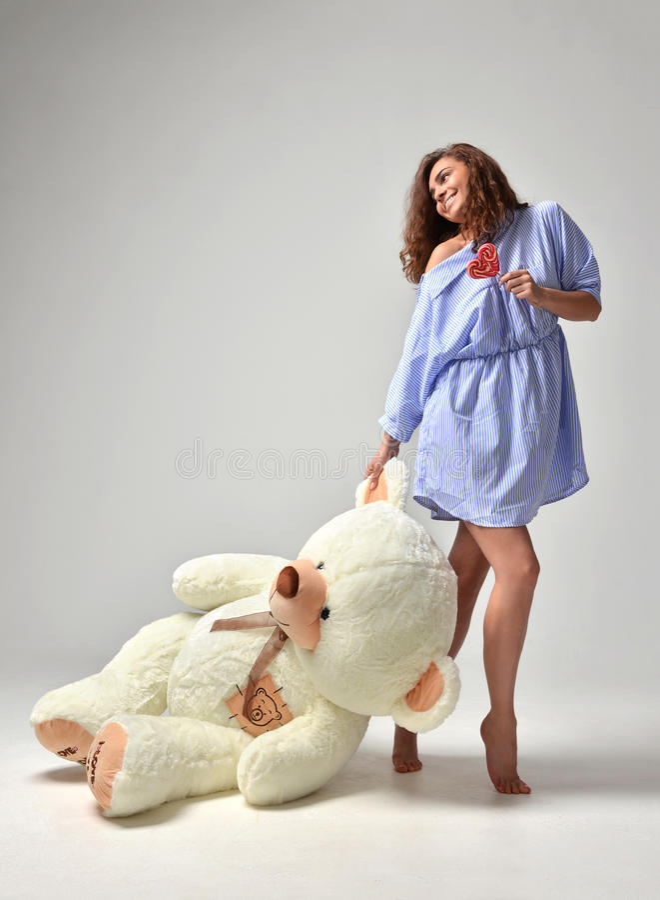 Młoda piękna dziewczyna z dużej miś miękkiej części zabawki szczęśliwy ono uśmiecha się obrazy stock