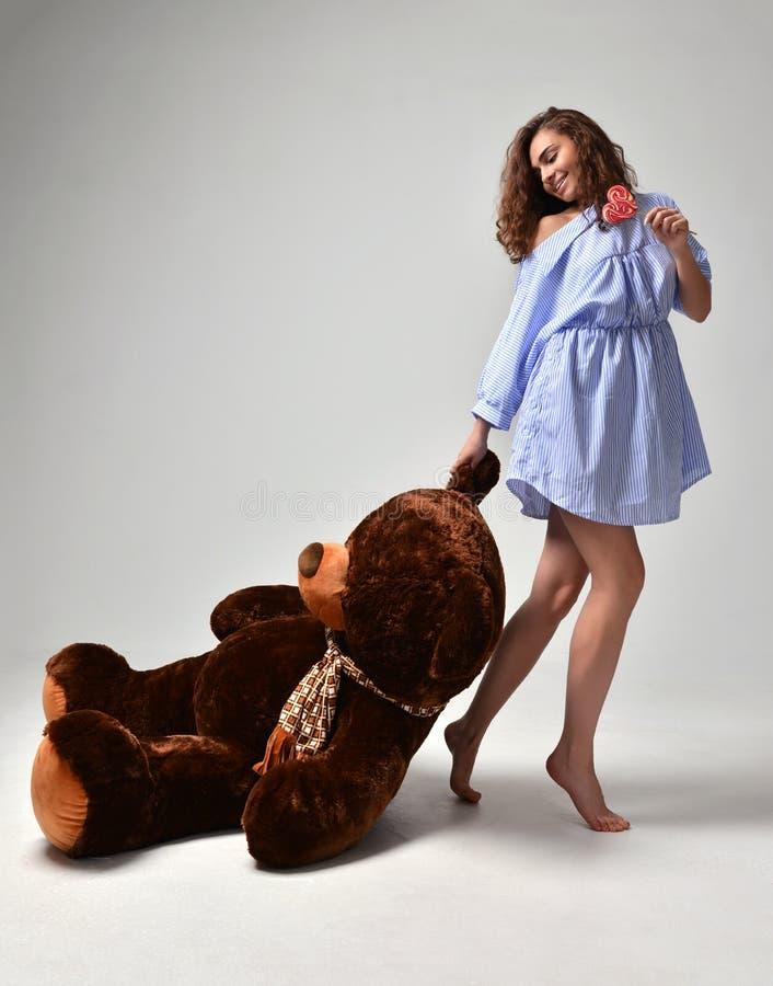 Młoda piękna dziewczyna z dużej miś miękkiej części zabawki szczęśliwy ono uśmiecha się fotografia royalty free